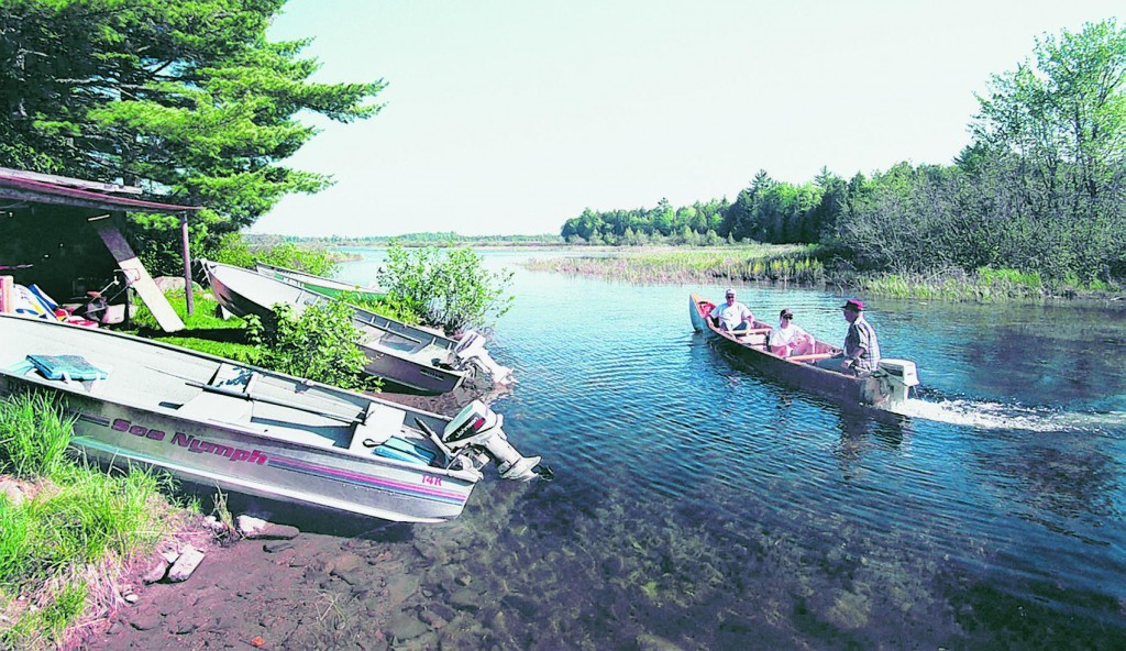 Fishermen and their guide head out onto Big Lake in Princeton for a day of smallmouth bass fishing from a camp on the shore of Grand Lake Stream.