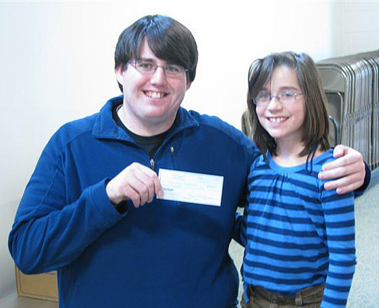Michael Blais, left, of Standish, coordinator of Catherine's Cupboard Food Pantry in Standish, receives a $500 check presented by Steep Falls Elementary School student Sydney Gillingham on behalf of the school's Parent Teachers Organization.