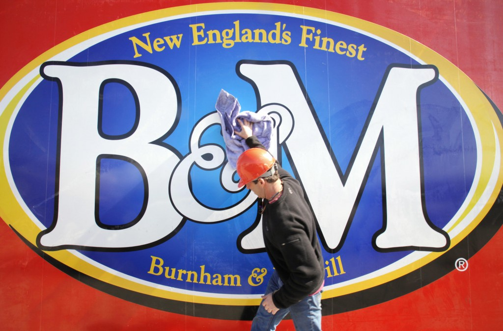 Kyle Noyes, with Sign One of Falmouth, wipes down the new B&M Baked Beans sign before it gets lifted into place at the top of the bean factory in Portland on Friday.