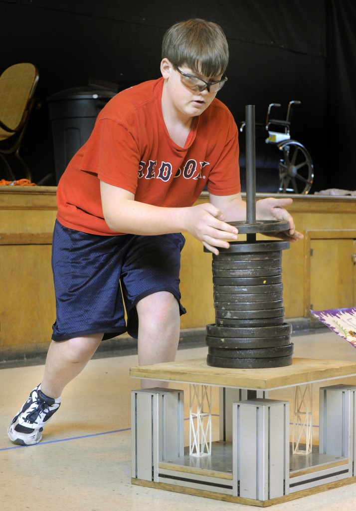 Brady Grotton from Jefferson Village School lowers weights down onto two balsa wood columns as his teammates perform a skit in the Column Structure challenge.