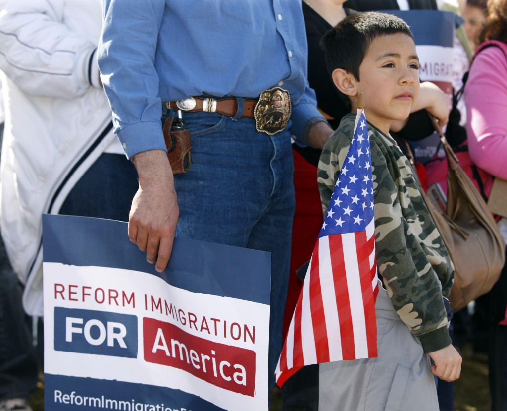 Eight-year-old Adrian Gomez carries an American flag during a rally in Denver on Sunday to spur lawmakers to reform immigration policies. The rally was part of a nationwide effort to bring attention to immigration issues.