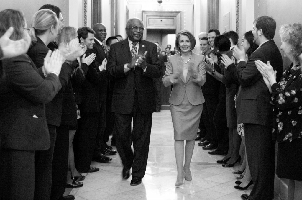 Speaker Nancy Pelosi of California is applauded as she walks with Rep. James Clyburn, D-S.C., after the House passed health care reform Sunday.