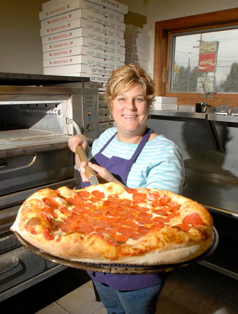 Darlene Walsh, owner of 8-Corners Pizza in Scarborough, displays a freshly made pepperoni pizza.