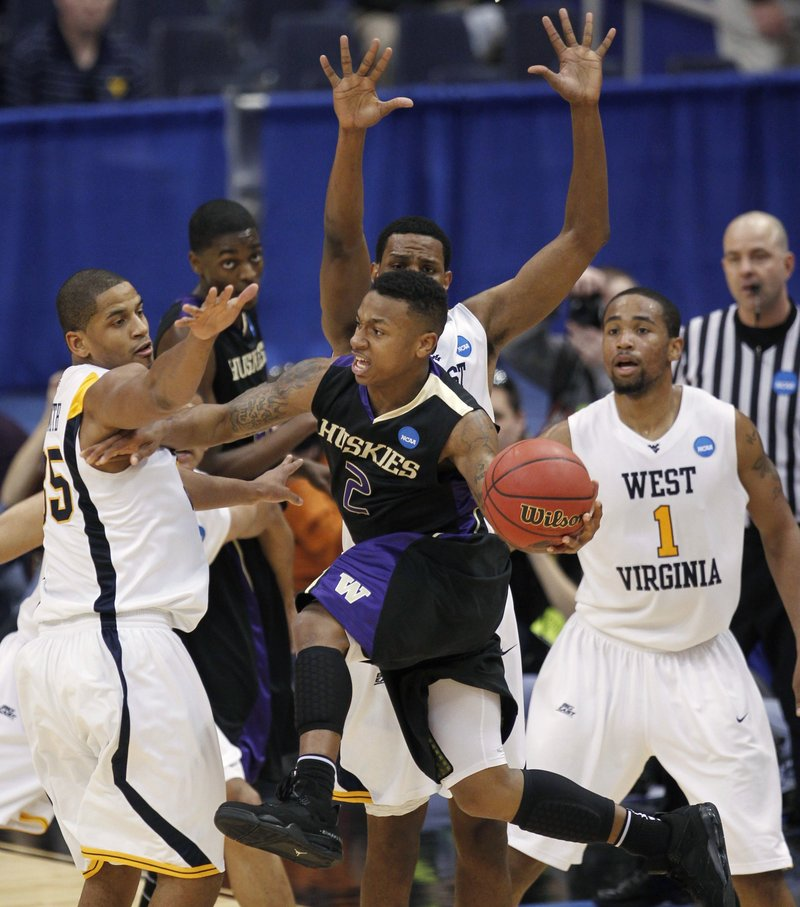 Isaiah Thomas of Washington looks to pass Thursday night as the West Virginia defense moves in during West Virginia's 69-56 victory in an East Regional semifinal.