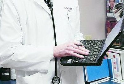 Dr. Joe Davison uses a computer tablet to access patient information at West Wichita Family Physicians in Wichita, Kan. Health care providers can recoup some of the costs of such systems.