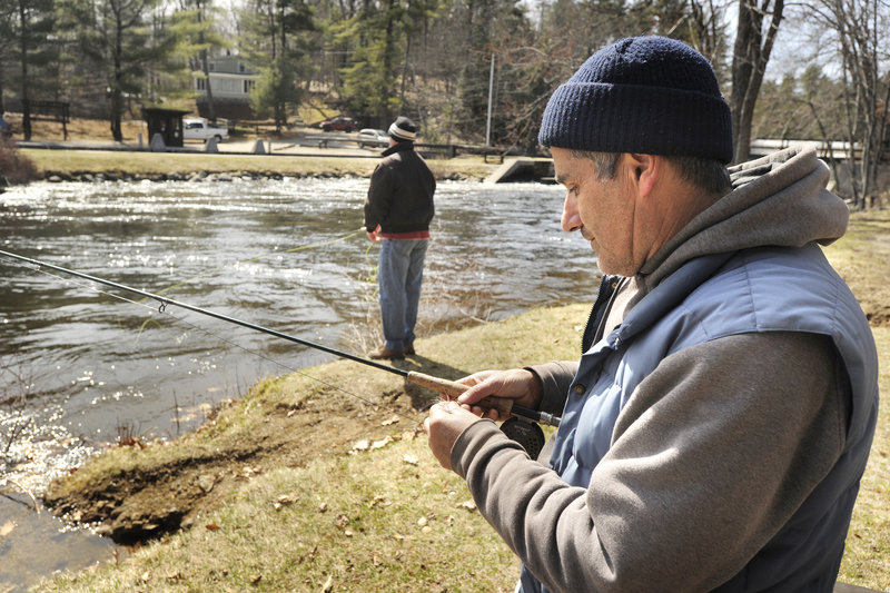 Stephen Sparaco, a Maine Guide from Standish, ties on a new fly before casting Friday at the Songo Locks in Naples. The area is typically lined with fishermen for the first days of the open-water season.