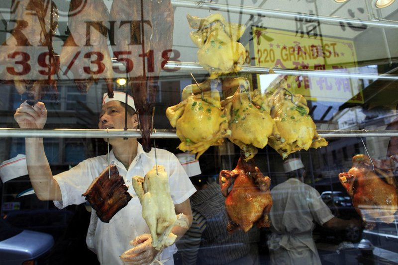 """A worker at a restaurant in the Chinatown neighborhood of Manhattan reaches for a pungent roasted duck hanging in the window Friday. Rockefeller University researchers spent five years creating a """"smell demography"""" of metropolitan New York City to sniff out what New Yorkers think is noxious or nice."""