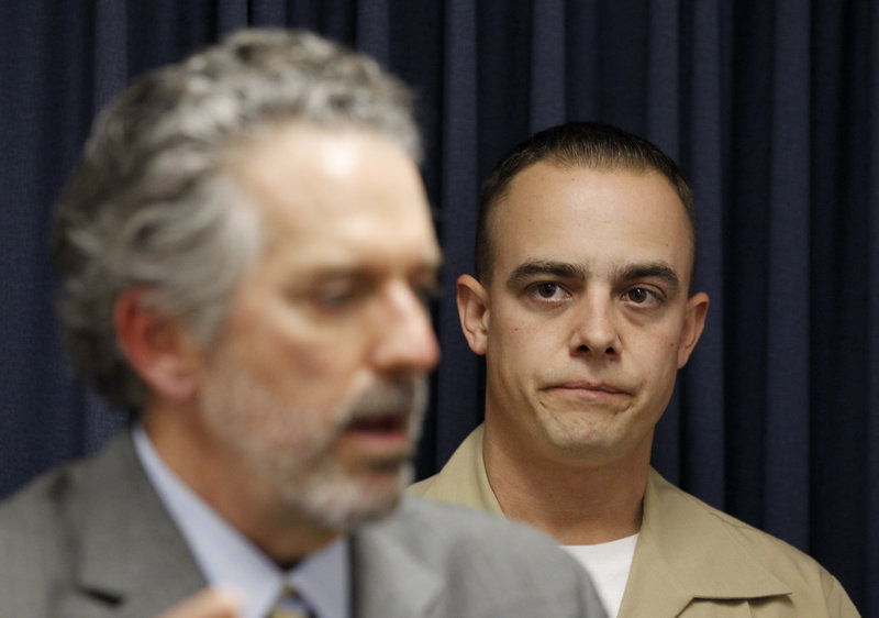 Marine Corps Staff Sgt. Frank Wuterich, right, listens as his attorney, Neal Puckett, talks to the media Friday.
