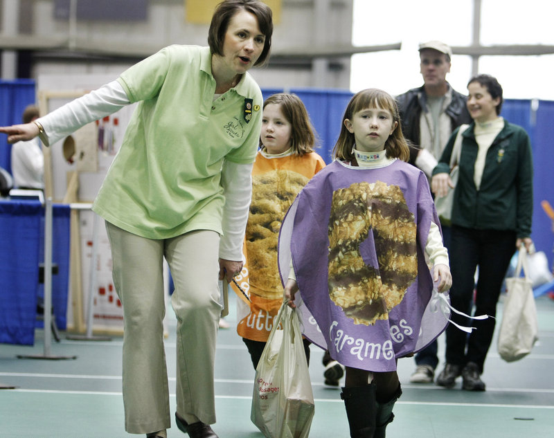 Kristin Larkin, a leader with Brownie Troop 1173 in Gorham, walks her daughter Kate Larkin, 8, and Brenna Donovan, 9, around to deliver Girl Scout Cookies to vendors at the Gorham Marketplace on Saturday at USM in Gorham.
