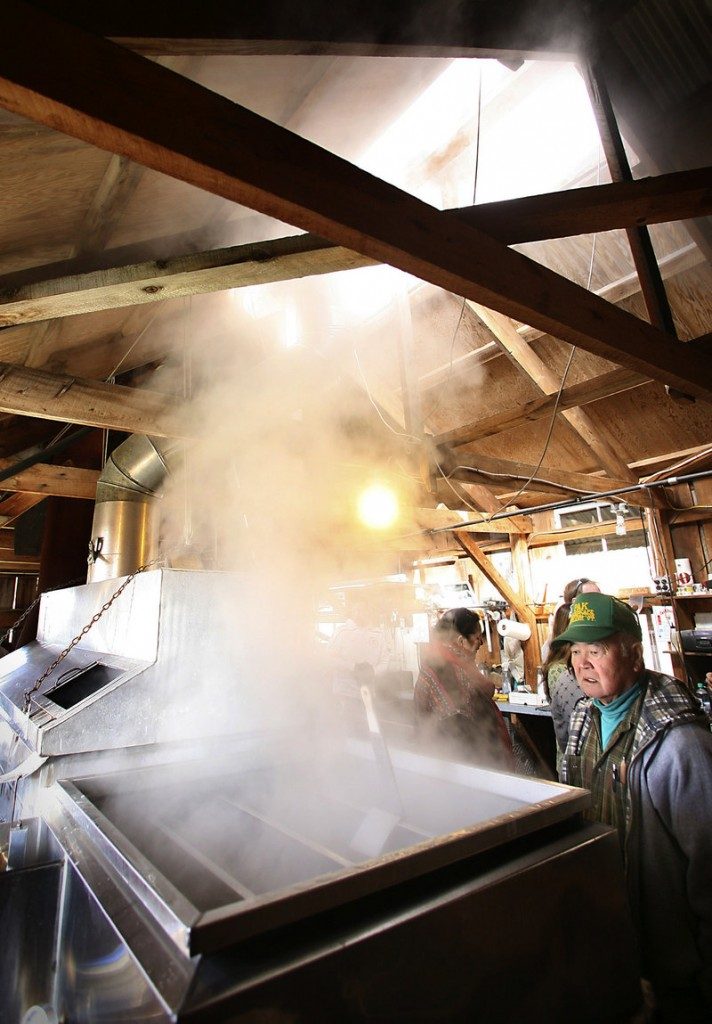 Jimmy Pak of Biddeford watches on Saturday as sap is boiled in the evaporator at Cole Farm. The boiling evaporates the water in the sap, leaving the syrup the farm sells, at left.