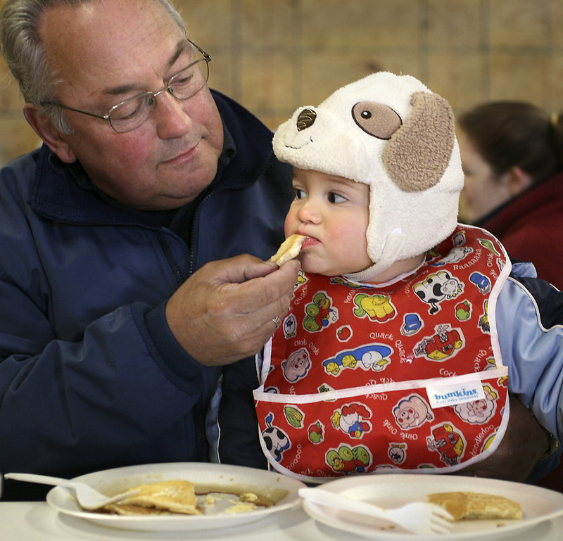 Malcolm Graffman of Saco feeds a piece of pancake to his 10-month-old grandson Quinn Purvizat. About 320 visitors tried Cole Farm's maple syrup on buttermilk pancakes Saturday.