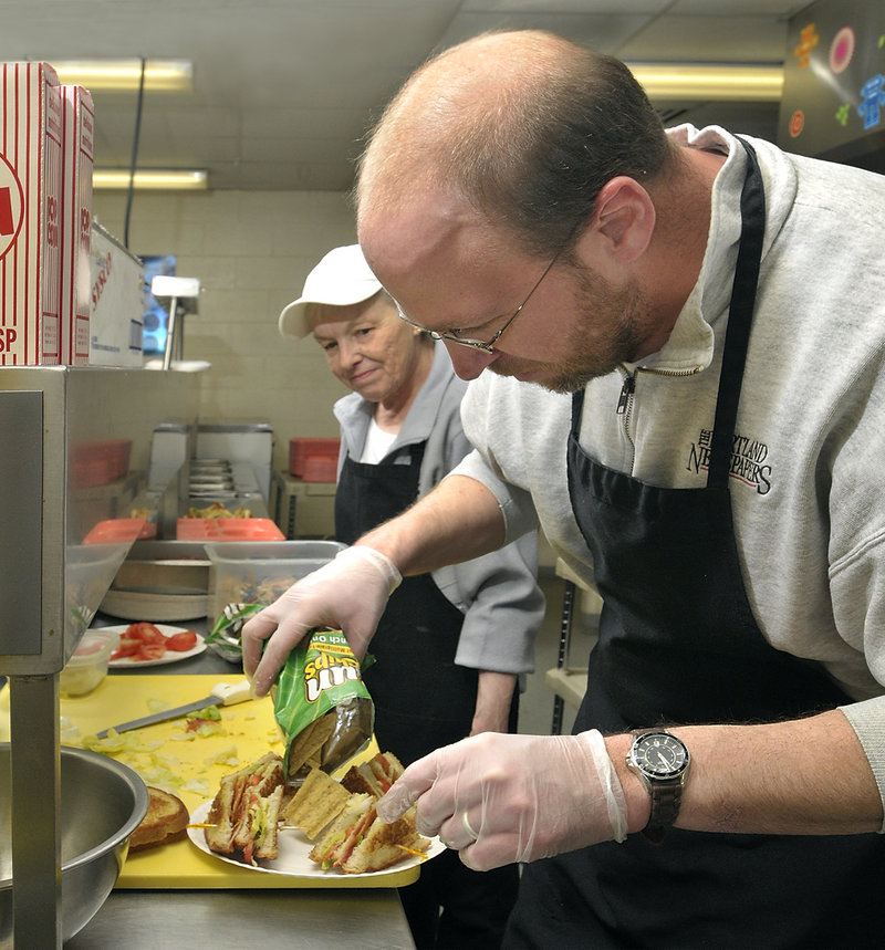 Under the watchful eye of Judy Levesque, Ray Routhier adds chips to the plate as he makes club sandwiches at the Cape Elizabeth Middle School cafeteria.