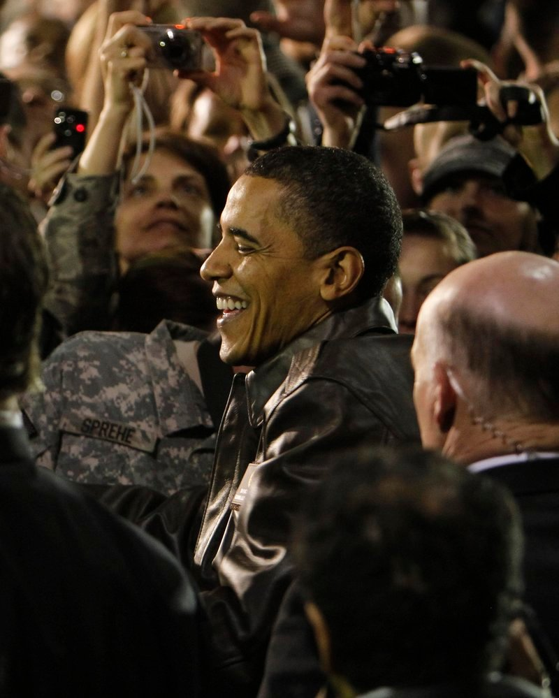 "President Obama is swarmed by U.S. troops at Bagram Air Base in Afghanistan on Sunday during a surprise visit. ""Your services are absolutely necessary ... to America's safety,"" he told the troops."