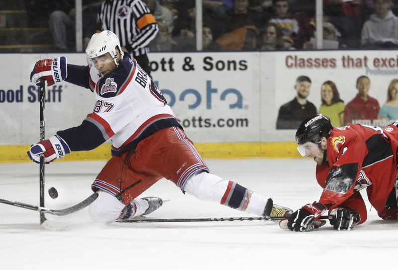 Drew Schiestel, right, of the Pirates dives in attempt to knock the puck away from Donald Brashear during Portland's 3-2 win Sunday over the Hartford Wolf Pack at the Cumberland County Civic Center.