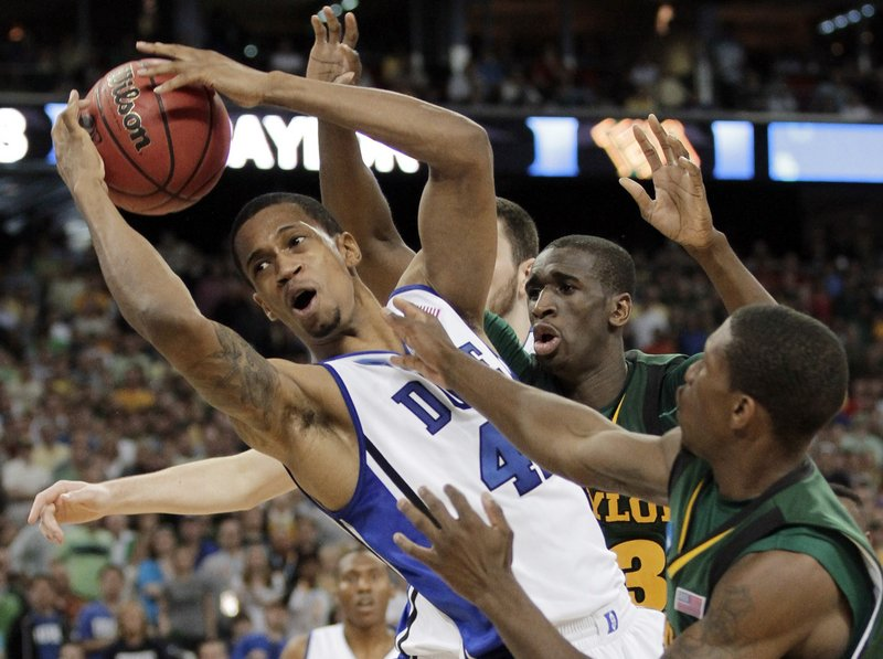 The Associated Press Lance Thomas of Duke pulls a rebound away from a crowd Sunday during a regional final against Baylor. Thomas had nine rebounds in Duke's win.
