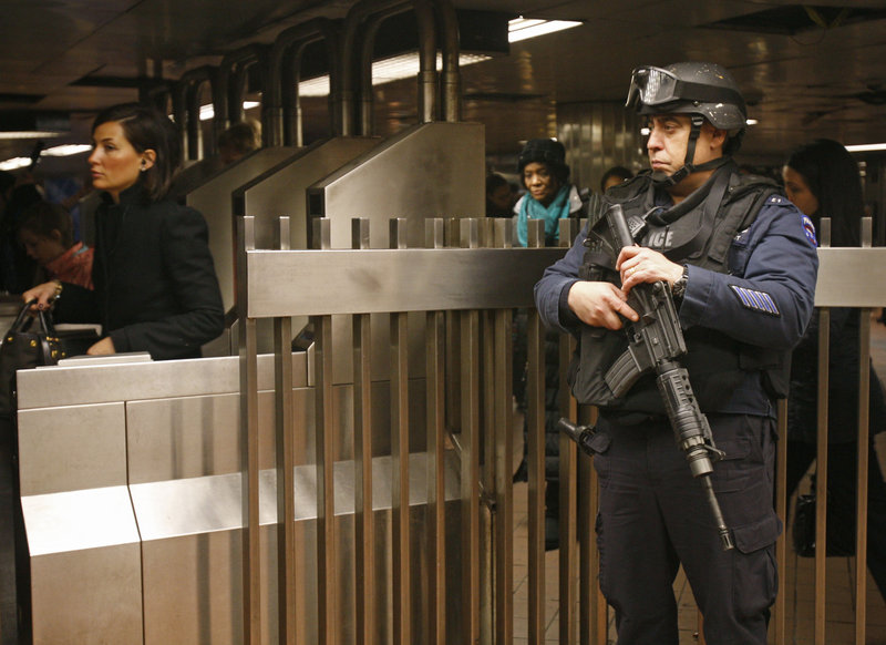 A counterterrorism officer stationed at Grand Central Station in New York keeps his eye on commuters at the subway turnstiles on Monday,