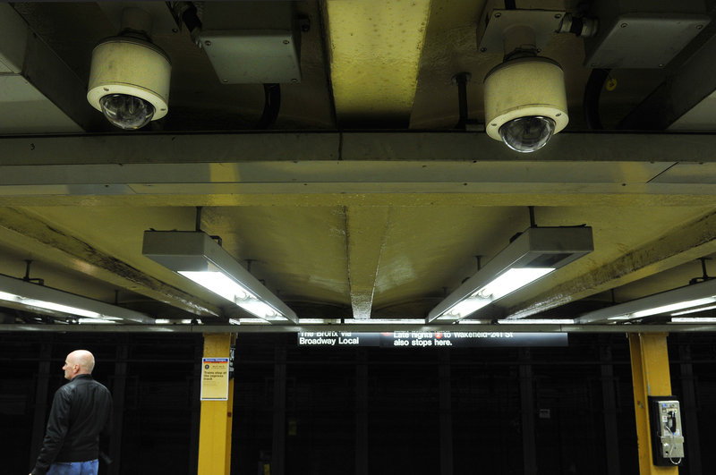 Two ceiling-mounted video cameras keep watch over the 34th Street station in New York. About half of the 4,313 cameras installed along the city's public transit system aren't operable, and cuts in the number of transit police patrols, possibly weakening city security.