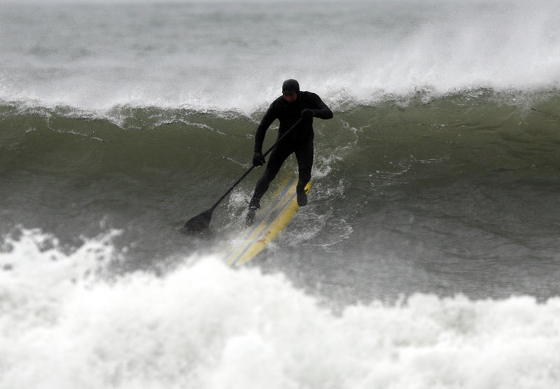 A paddle surfer heads down a wave before falling into the ocean while taking advantage of heavy, storm-driven surf along Kennebunk Beach on Tuesday.