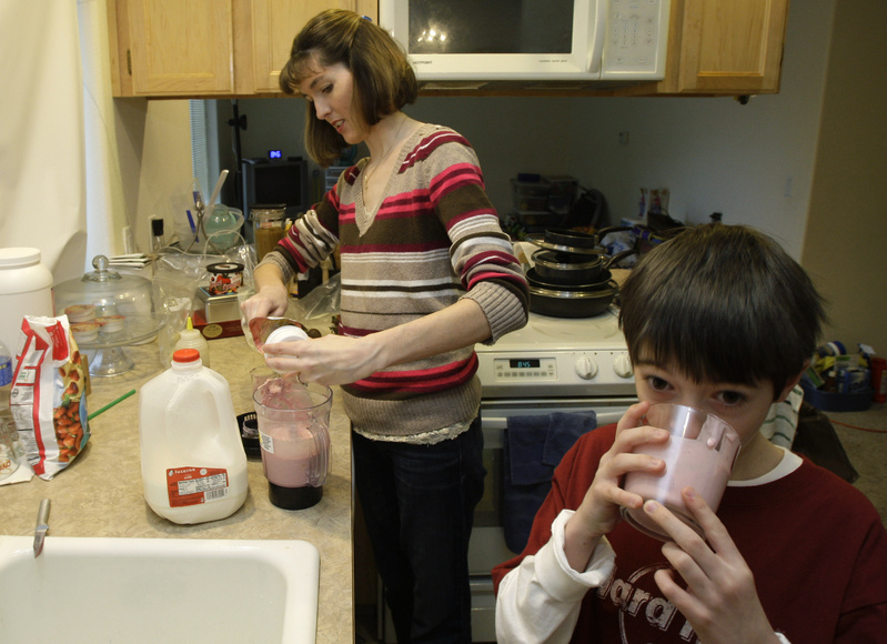 Nicole Rosen serves her son Austin Meyers, 8, a homemade smoothie at their home in Roy, Wash. Despite the difficult economy, Rosen says she and her husband have tried build up their savings and avoid credit card and other interest charges.