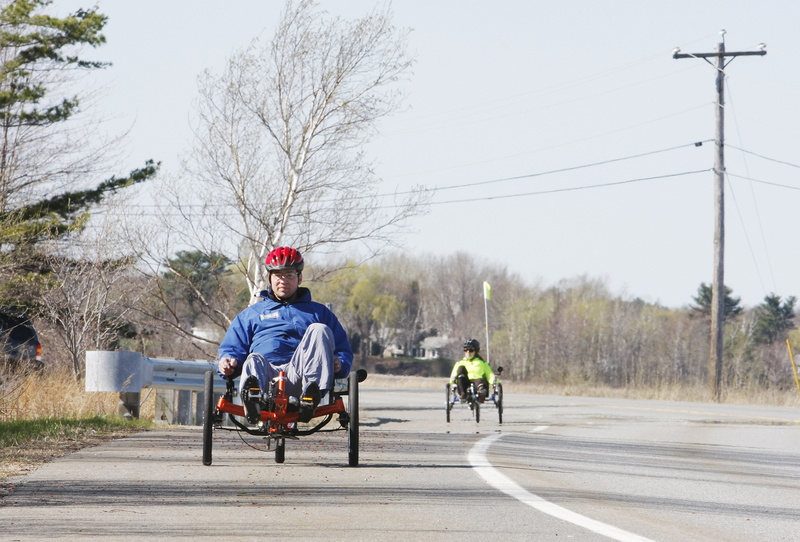 Ethan Davis, owner of Wildfire Human Powered Vehicles, foreground, and reporter Deirdre Fleming ride recumbent tricycles alongside Scarborough Marsh recently.