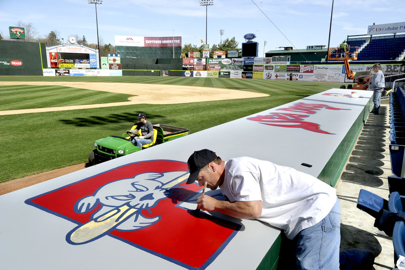 Sun-drenched Hadlock Field buzzes with activity Tuesday as workers get the field, dugouts and stands ready for the Portland Sea Dogs home opener Thursday. Painting the team logo on top of the home dugout are Mike Daigle, left, and Anthena Court.