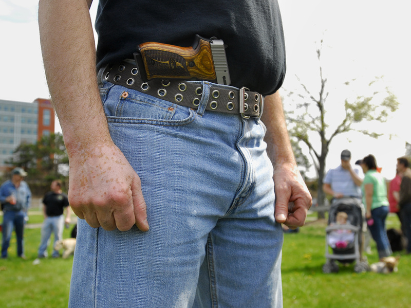 A pro-gun demonstrator who did not want to be identified stands in a park at Back Cove in Portland during an open-carry gathering Sunday to publicize the right to carry unconcealed weapons.