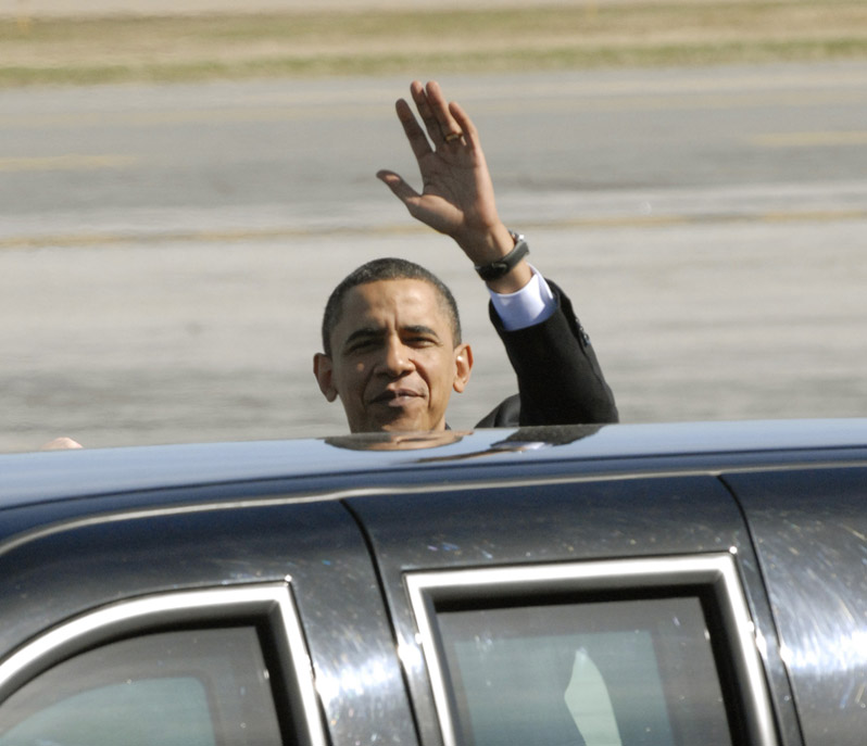 President Obama waves to the media before getting into his limo after landing at the Portland Jetport.