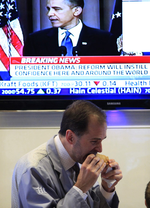 A trader eats lunch at the New York Stock Exchange during President Obama's speech today.