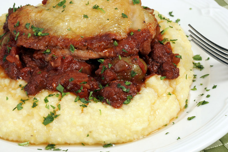 polenta topped with braised chicken and sausage with green olives.