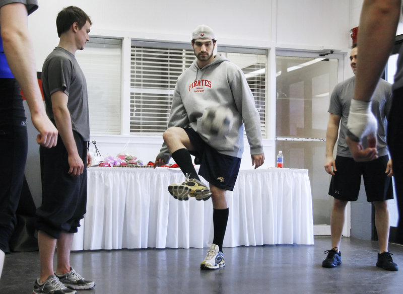 Mark Mancari of the Portland Pirates is watched by teammate J.P. Lamoureux while doing a pregame ritual of two-touch soccer at the Civic Center. The same group of players takes part before each game.