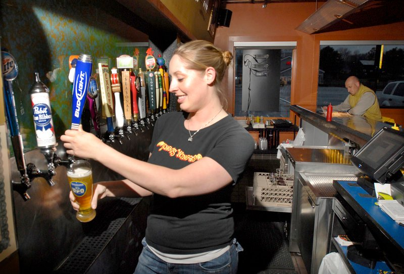 Bartender Sarah Hewes pours at Binga's Wingas in Yarmouth, where there's always a beer special and you can choose from more than 20 flavors of sauce for chicken wings and tenders.
