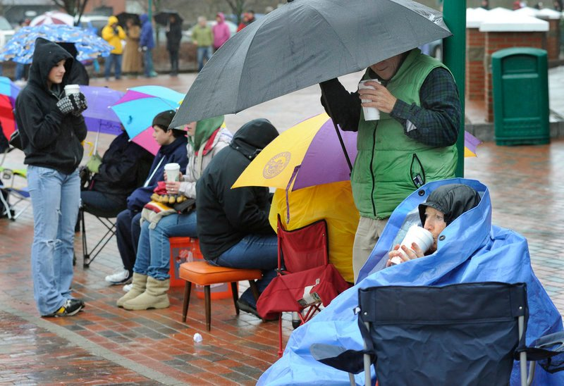 Hot coffee helps Saco resident Madelyn Belliveau, right, stay warm as she waits in line Wednesday for tickets to see President Obama. Belliveau said she arrived at 5:45 a.m. Ticket distribution began at 11 a.m.