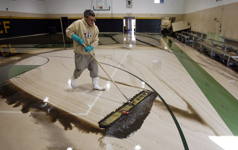 Ron Chopoorian, a volunteer at Cranston League for Cranston's Future, a boys and girls youth organization, sweeps water out of the gymnasium Friday after flooding from the Pawtuxet River left the gym under 4 feet of water.