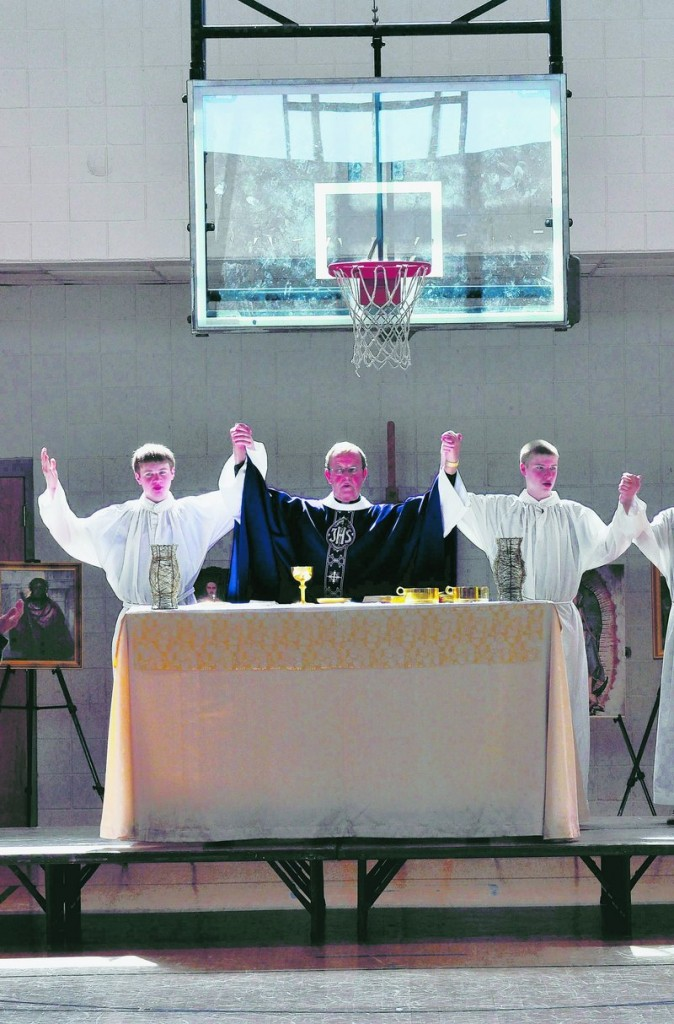"St. Matthew's Monsignor John McSweeney, center, leads Sunday Mass in the parish center gym in Charlotte, N.C. ""Catholic services do not function without a priest present,"" he notes."