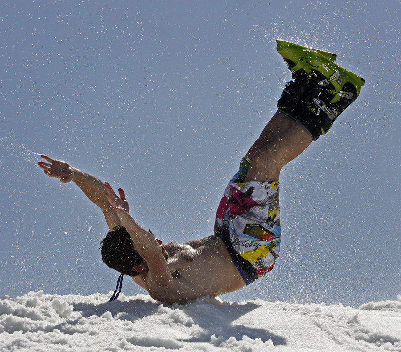 Tony Blout, a senior at Bowdoin College, slides onto the snow after crossing the pond on one ski.