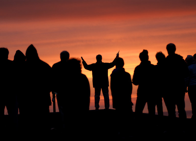 The Rev. John McCall, center, senior minister of First Congregational Church, United Church of Christ in South Portland, leads an Easter sunrise service at Fort Williams Park in Cape Elizabeth on Sunday.