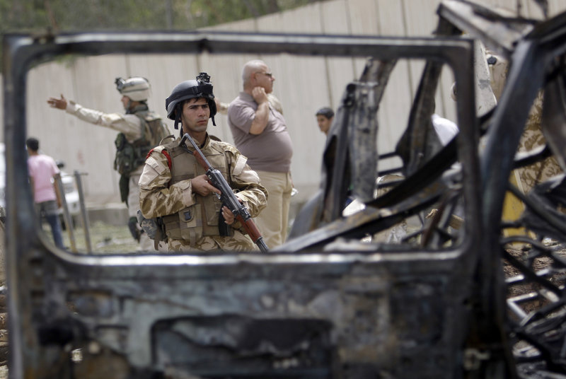 Iraqi security forces inspect the site of a car bomb attack near the Iranian Embassy in Baghdad. Three explosions in quick succession killed more than 40 people.