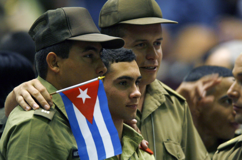 Elian Gonzales, center, poses for a photo at the Young Communist Union congress in Havana. Ten years ago this month, he was removed from the home of relatives in Miami and returned to Cuba.