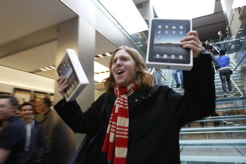 Andres Schobel holds up two iPads as one of the first customers to buy the electronic tablet on the first day of sales at an Apple Store in San Francisco on Saturday. Apple said Monday that it delivered more than 300,000 iPads on its opening day.
