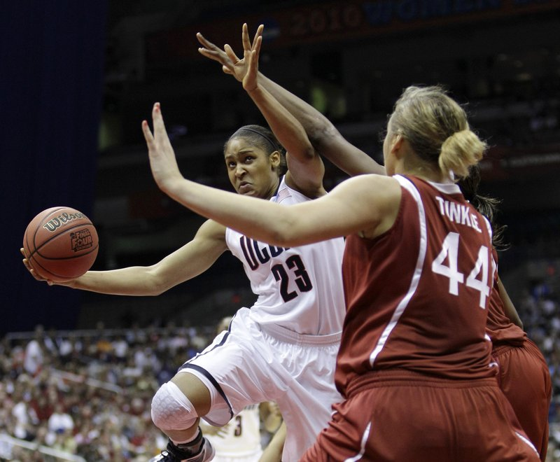 Maya Moore of Connecticut battles her way to the basket as Stanford's Joslyn Tinkle moves into her path. Moore had 23 points and 11 rebounds and the Huskies came on in the second half to beat the Cardinal 53-47 for the title.