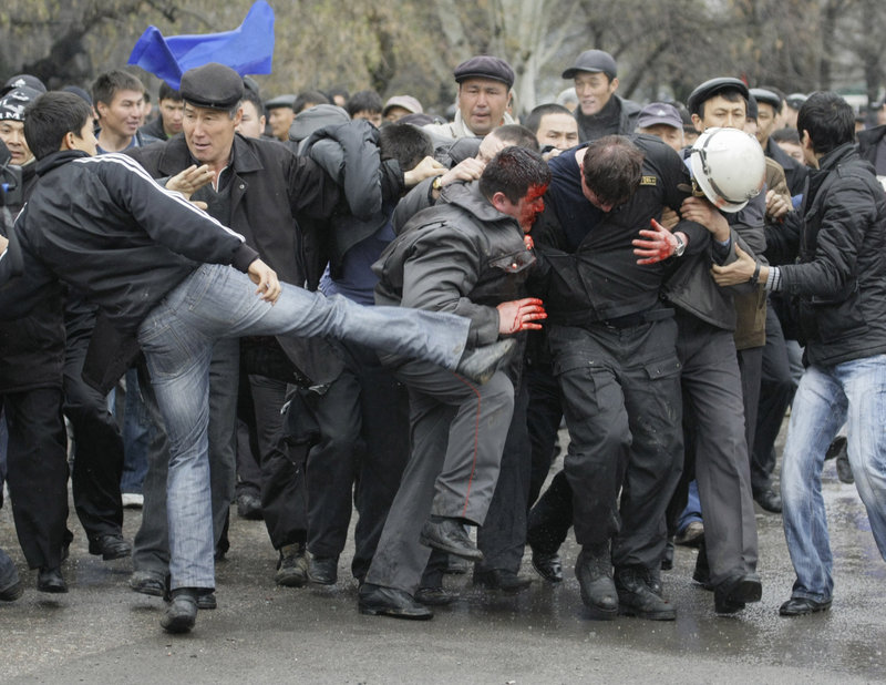 A protester kicks at police Wednesday in Bishkek, Kyrgyzstan. Opposition leaders have called for the closure of a U.S. air base that serves as a key transit point for supplies essential to the war in nearby Afghanistan.