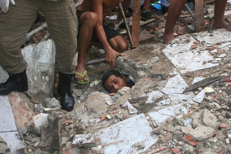 Carlos Eduardo Silva dos Santos, 24, peers out from under a wall where he is trapped, as rescue workers try to free him Wednesday in Rio de Janeiro. About 11 inches of rain fell in 36 hours.