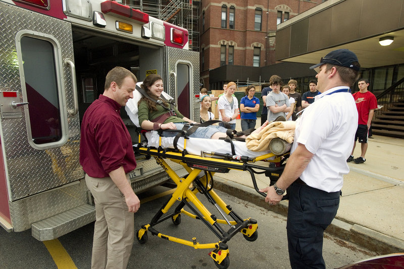 At a recent session focusing on ambulance- and rescue-related careers, Butch Russell (left), clinical director for North East Mobile Health Services, and paramedic Don Bouchard demonstrate the use of their high-tech stretcher to Kelsey Leeman and the other Explorers.