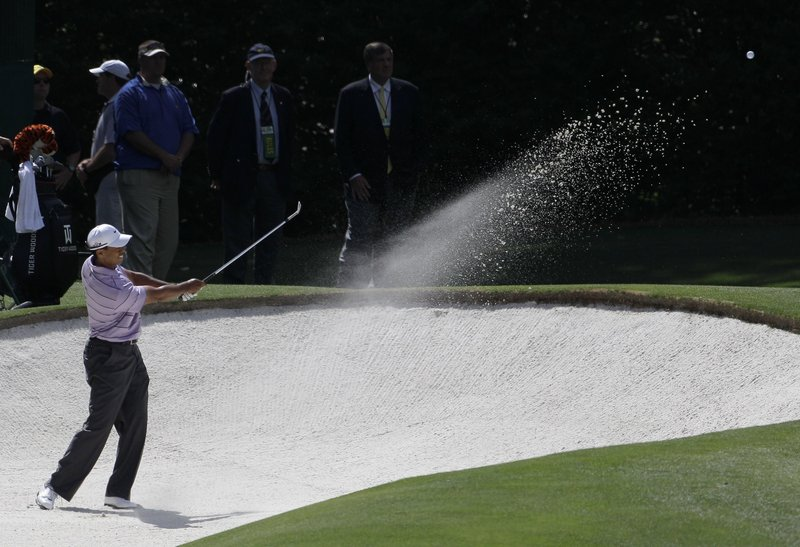 Tiger Woods blasts out of a bunker on the fourth hole, leading to one of his five bogeys in the third round. But Woods scrambled for a 2-under 70 and was tied for third, four strokes behind Lee Westwood.