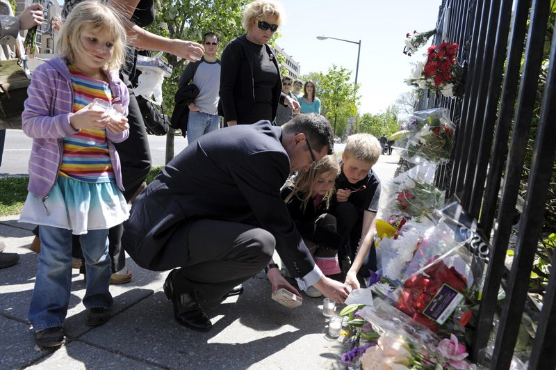 Mourners place lighted candles for President Lech Kaczynski and his wife, Maria, on Saturday at the gate of the Polish Embassy in Washington.