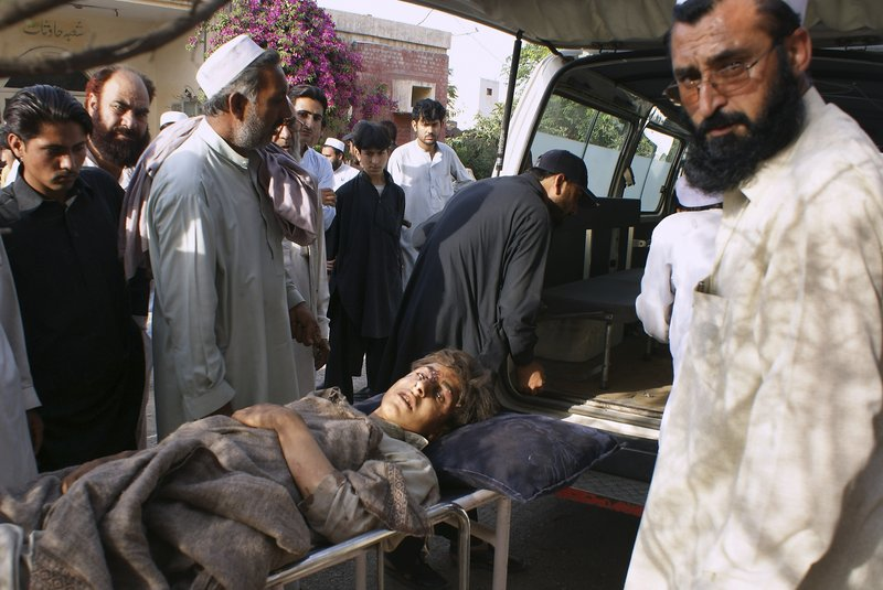 Pakistani tribesmen accompany a boy injured in strikes by Pakistani military jets as he arrives at a hospital on the outskirts of Peshawar on Saturday.