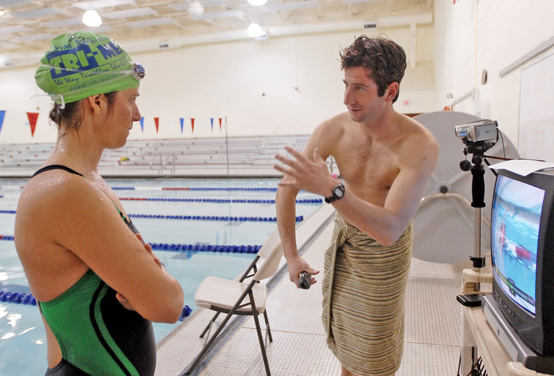 Will Thomas of Tri-Maine offers advice to Dena MacVane after watching video of MacVane swimming as part of the triathlete clinic.