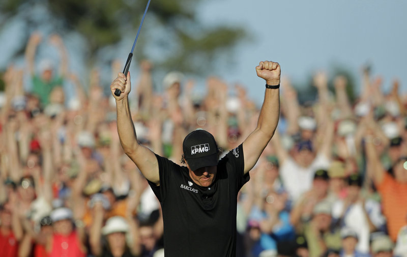 After sinking an 8-foot birdie putt on the final hole Sunday, Phil Mickelson raises his arms in celebration of his three-shot victory in the Masters at Augusta, Ga. Mickelson finished with a 5-under-par 67 to earn his third green jacket and fourth major title overall.