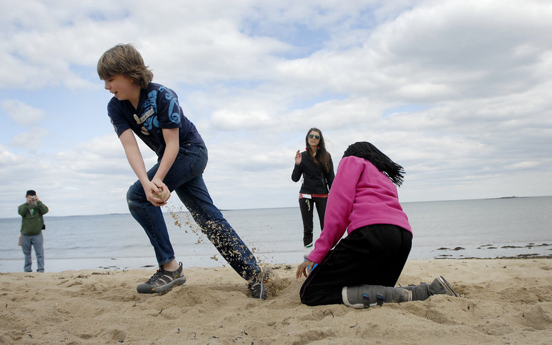 Lucien Cheney takes sand from a bucket as Tshephiso Tselele puts sand back as part of a relay drill that was aimed at showing how the ocean waves shift beach sand, during Lincoln Middle School's visit to the Ferry Beach Ecology School in Saco on Monday.
