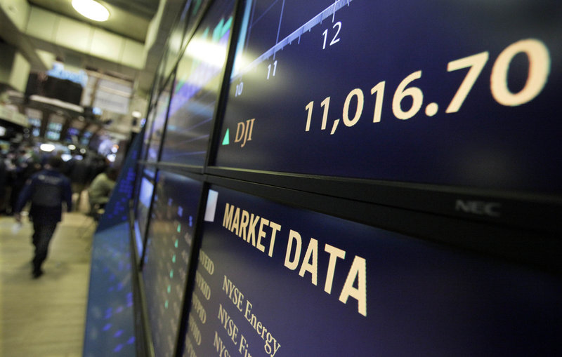 A board on the floor of the New York Stock Exchange shows the Dow Jones industrial average above 11,000 after the opening bell Monday. The closed above 11,000 for the first time in a year and a half.